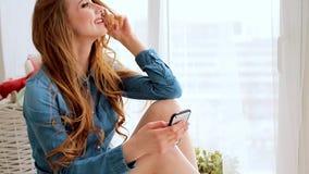 Toevallige jonge vrouw die mobiele telefoon met behulp van terwijl het liggen in bed thuis in een daglicht stock videobeelden