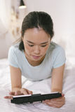Toevallige jonge vrouw die op bed liggen en digitale tablet thuis gebruiken Stock Foto