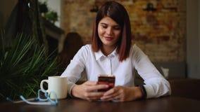 Toevallige jonge vrouw die op telefoon spreken die gesprek via het videobureau van de praatjeconferentie thuis hebben Onderneemst stock footage