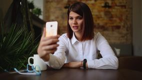 Toevallige jonge vrouw die op telefoon spreken die gesprek via het videobureau van de praatjeconferentie thuis hebben Onderneemst stock video