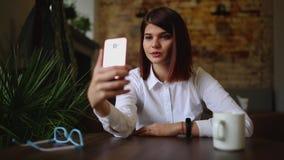Toevallige jonge vrouw die op telefoon spreken die gesprek via het videobureau van de praatjeconferentie thuis hebben Onderneemst stock videobeelden