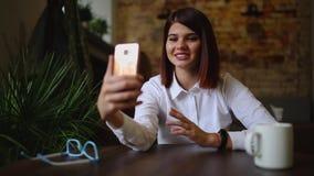 Toevallige jonge vrouw die op telefoon spreken die gesprek via het videobureau van de praatjeconferentie thuis hebben Onderneemst