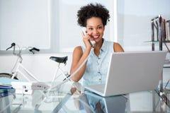 Toevallige jonge vrouw die telefoon en laptop met behulp van Stock Afbeeldingen