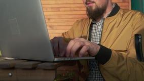 Toevallige kerel die aan PC buiten werken stock footage
