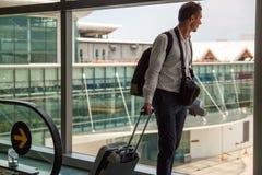 Toevallige mannelijke passagier die de handbagagezak dragen, die de vliegtuig het inschepen gang lopen stock fotografie
