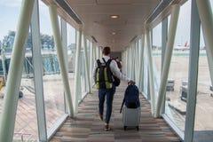 Toevallige mannelijke passagier die de handbagagezak dragen, die de vliegtuig het inschepen gang lopen stock afbeelding