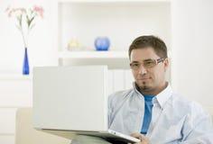 Toevallige mens die laptop met behulp van Royalty-vrije Stock Afbeelding