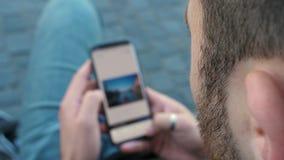 Toevallige mens het uitgeven foto op zijn telefoon stock videobeelden