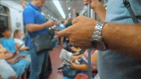 Toevallige mensenlezing van het mobiele scherm van telefoonsmartphone terwijl blikken de navigator die op metro in de metro reize stock videobeelden
