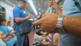 Toevallige mensenlezing van het mobiele scherm van telefoonsmartphone terwijl blikken de navigator die op metro in de metro reize stock footage