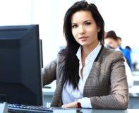 Toevallige onderneemster die laptop in bureau met behulp van Stock Foto's