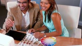 Toevallige ontwerper die fotosteekproef en kleurensteekproef bekijken stock videobeelden