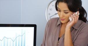 Toevallige Spaanse bedrijfsvrouw die op mobiele telefoon in bureau spreekt Stock Afbeeldingen