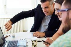 Toevallige stafmedewerkers die op een vergadering met laptop samenwerken royalty-vrije stock fotografie