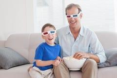 Toevallige vader en zoon die op een 3d film letten Stock Afbeeldingen