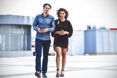 Toevallige vergadering buiten op een zonnige dag Paar die tussen verschillende rassen bij straat lopen stock afbeelding