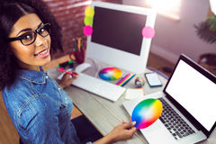 Toevallige vrouwelijke ontwerper die en kleurengrafiek glimlachen houden stock fotografie