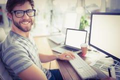 Toevallige zakenman die computer in bureau met behulp van stock foto's