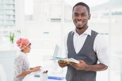 Toevallige zakenman die en notitieboekje glimlachen houden Stock Afbeeldingen