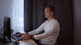 Toevallige zakenman die thuis, zittend bij bureau, typend aan toetsenbord werken, die het computerscherm bekijken Grijs gordijn o stock videobeelden