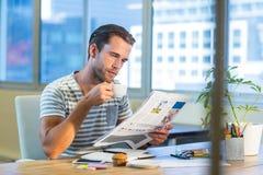 Toevallige zakenman het drinken koffie en het lezen van tijdschrift bij zijn bureau stock fotografie