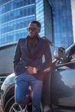 Toevallige zwarte mens in zonnebril die dichtbij auto in stad stellen royalty-vrije stock foto's