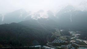 Toevlucht bij voet bergen in bewolkt weer Toneel hoogste mening van berglandschap met sneeuwpieken in mist en klein stock video