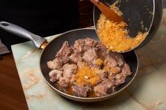 Toevoegend gebraden ui in het braden van vlees. Stock Afbeelding