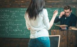 Toewijding aan het onderwijs De man onderwijst vrouw achtermening Leraar en studente in klaslokaal Onderwijs op universiteit of stock foto
