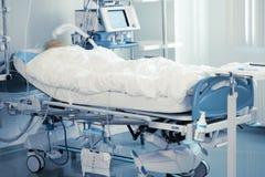 Toezicht op comateuze patiënt in intensive care stock afbeelding