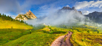 Tofane mountain range at sunny foggy morning. Panorama from Falzarego pass. Dolomites mountains, Italy, Europe. royalty free stock image