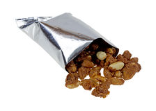 Toffee peanuts spilling from bag Stock Photo