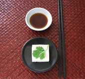 Tofu on a black dish. A square of tofu topped with a single cilantro leaf on a black dish with a white dish of soy sauce and black chopsticks against a dark red Royalty Free Stock Images