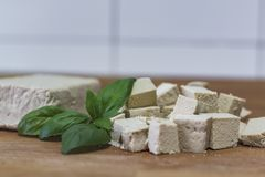 Tofu block and cubes of tofu on wooden cutting board royalty free stock photo