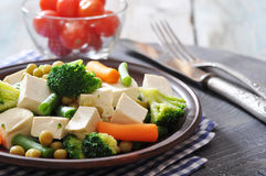 Tofu with  boiled vegetables. On plate closeup Royalty Free Stock Images