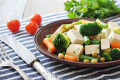 Tofu with  boiled vegetables. On plate and tomatos closeup Royalty Free Stock Photos