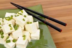 Asian vegetarian food : Tofu cubes with chopsticks close up Royalty Free Stock Images