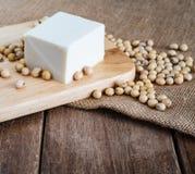 Tofu giapponese molle bianco fresco sul piatto di legno con il fagiolo della soia sul panno di sacco dell'iuta fotografia stock libera da diritti