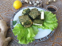 Tofu in green nettles tempura, on a plate with lettuce. Cooking vegetarian food with nettles and quail eggs royalty free stock photo