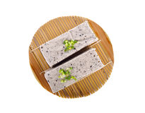 Tofu mix black sesame seeds on bamboo mat with white background Stock Images