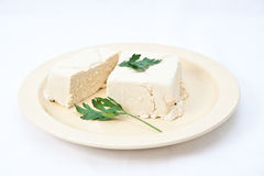 Tofu on a plate. With white background and a few leaves of parsley Royalty Free Stock Photography