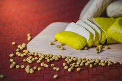 Tofu is sliced on a wooden cutting board. stock images