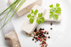 Tofu slices with parsley, salt, pepper and old knife on white background Royalty Free Stock Photography