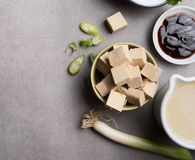 Tofu , soy sauce, and broth for asian food cooking on gray concrete background, top view, place for text. Vegetarian food or Asian cuisine concept stock photography