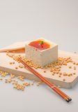 Tofu with Soya Sauce Dressing. Soya beans, chopsticks on chopping board and white background Royalty Free Stock Photo