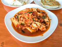 Tofu stir fry. Spicy tofu stir fry on white plate on wood table in restaurant Royalty Free Stock Image