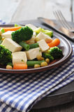 Tofu with vegetables. Tofu with  boiled vegetables on plate closeup Stock Image