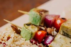 Tofukebab på hirs med mandlar, hirsappeller och tranbär Arkivbild