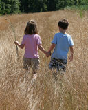 Together. A boy and a girl holding hands in a field Stock Images
