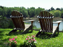 Together. Two adirondack chairs overlook the water of the Delaware River Royalty Free Stock Images